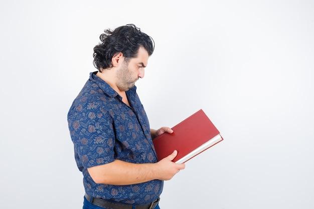 Retrato de homem de meia-idade olhando para um livro de camisa e olhando de frente com atenção
