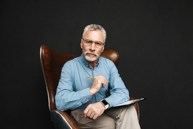Retrato de homem de meia idade profissional 50 anos com cabelos grisalhos e barba, trabalhando com documentos enquanto está sentado na poltrona de madeira no escritório, isolado sobre a parede preta