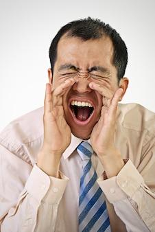 Retrato de homem de negócios a gritar com a boca aberta na parede branca.