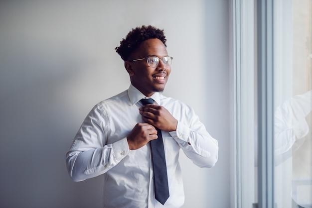 Retrato de homem de negócios afro-americano sofisticado que está ao lado da janela e que ajusta sua gravata.