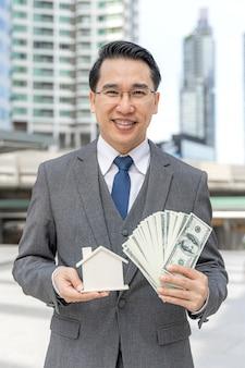 Retrato de homem de negócios asiático segurando dinheiro, notas de dólar e casa modelo no distrito comercial