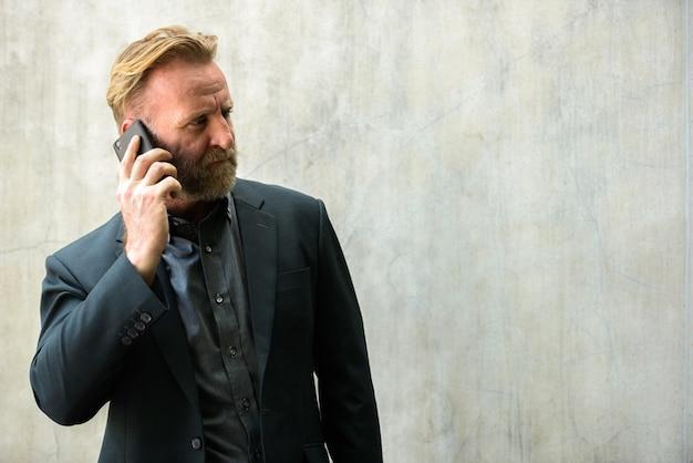 Retrato de homem de negócios barbudo bonito maduro com cabelo loiro em um terno contra uma parede de concreto ao ar livre