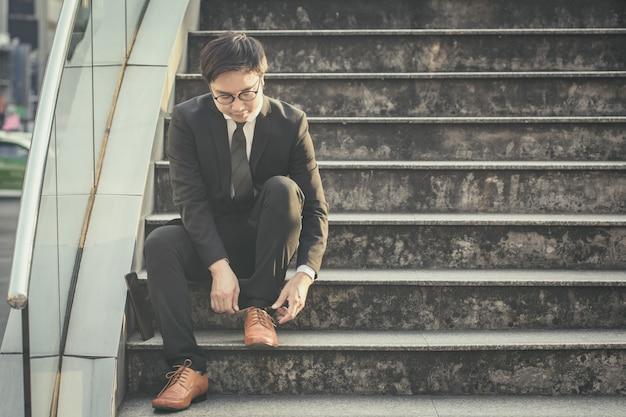 Retrato de homem de negócios bonito amarrar sapato na escada