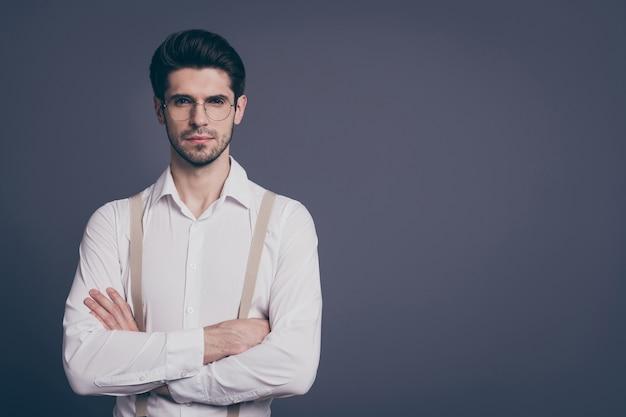 Retrato de homem de negócios bonito mãos cruzadas chefe estrito vestido formalwear camisa branca bege suspensórios especificações.