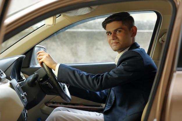 Retrato de homem de negócios indiano jovem, dirigindo um carro