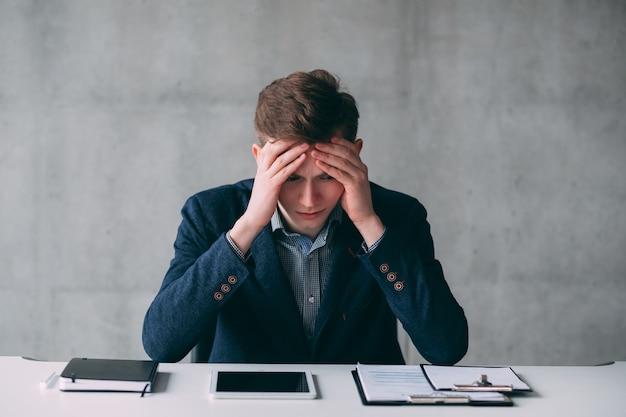Retrato de homem de negócios jovem com problemas financeiros. cara sentado na mesa, segurando a cabeça. expressão facial estressada.