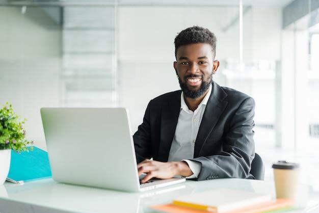Retrato de homem de negócios jovem negro africano bonito trabalhando no laptop na mesa de escritório
