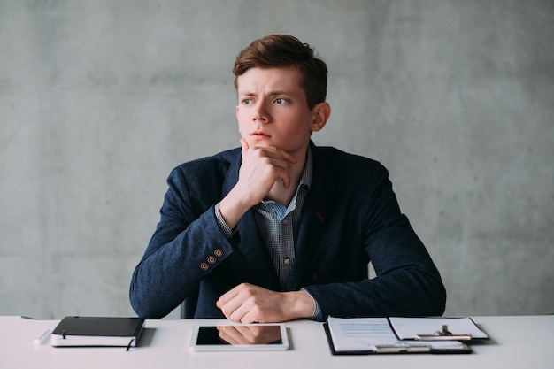 Retrato de homem de negócios jovem sentado na mesa sobre o fundo da parede cinza, gerando ideias. expressão facial pensativa.