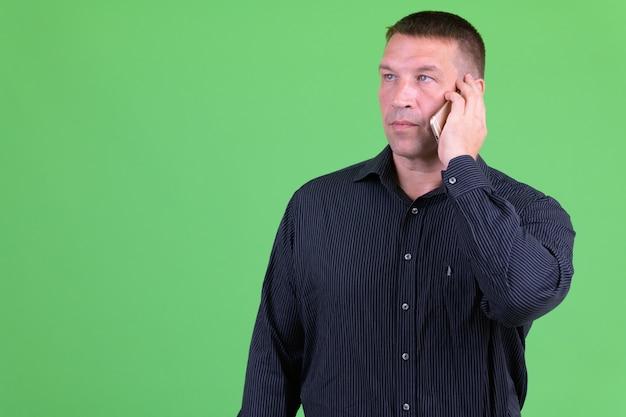 Retrato de homem de negócios machista maduro contra chroma key com parede verde