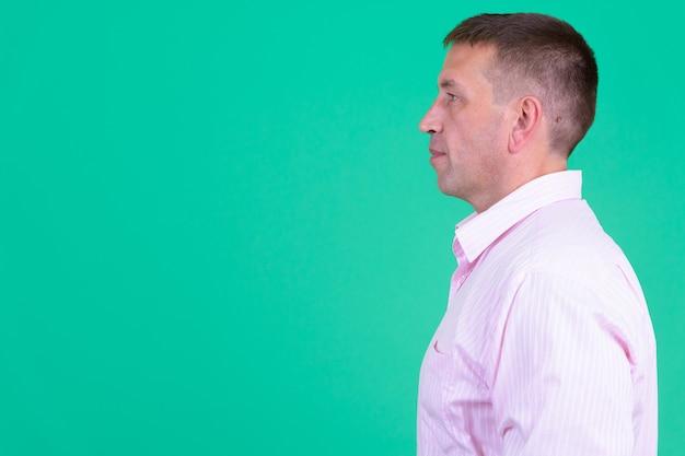 Retrato de homem de negócios machista maduro vestindo uma camisa rosa contra uma parede colorida