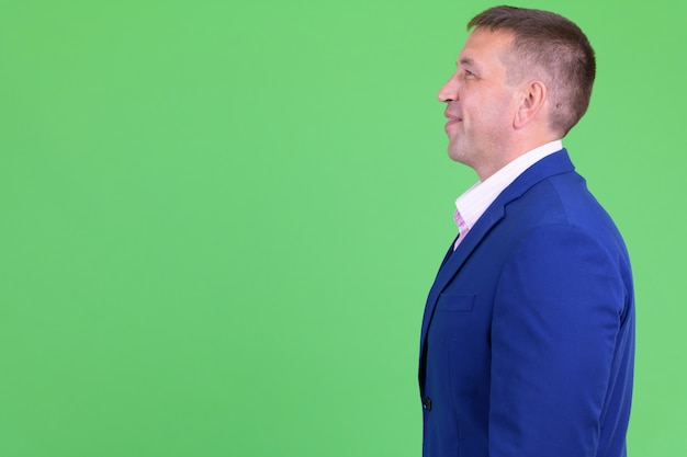 Retrato de homem de negócios macho maduro vestindo terno azul contra chroma key com parede verde