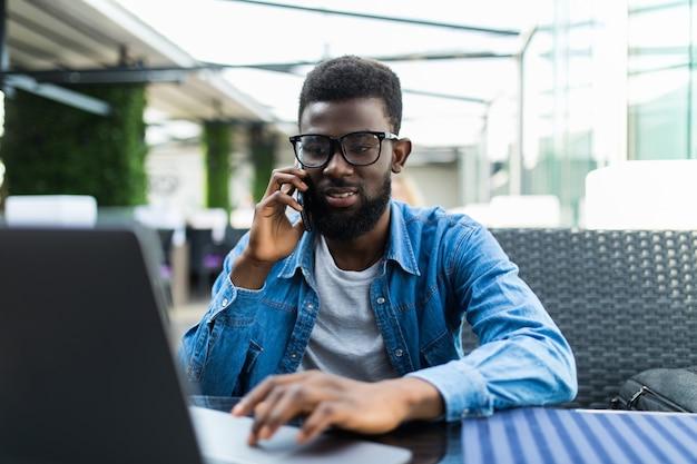 Retrato de homem de negócios na áfrica falando no telefone com o laptop na frente dele na mesa
