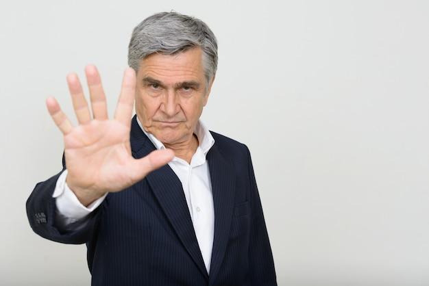 Retrato de homem de negócios sênior bonito em terno mostrando gesto de parada