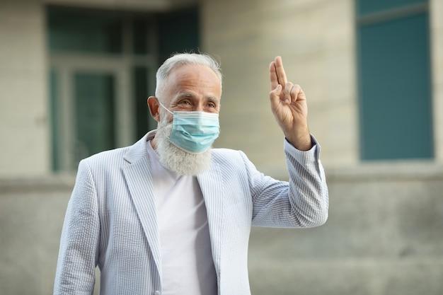 Retrato de homem de negócios sênior bonito positivo com máscara médica, sorrindo amigável e acenando com a mão