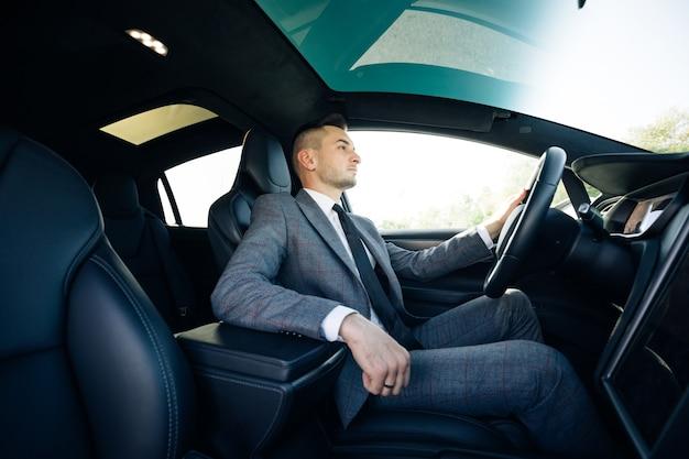 Retrato de homem de negócios sentado ao volante de um carro