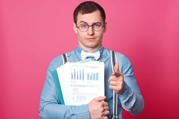 Retrato de homem de negócios sério com documentos nas mãos