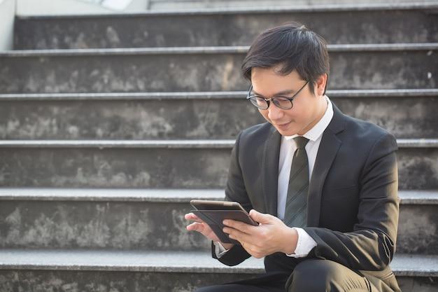 Retrato de homem de negócios sorridente parece confiante usando tablet computador