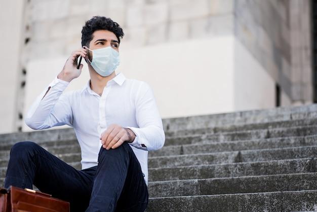 Retrato de homem de negócios usando máscara facial e falando ao telefone enquanto está sentado na escada ao ar livre. conceito de negócios. novo conceito de estilo de vida normal.