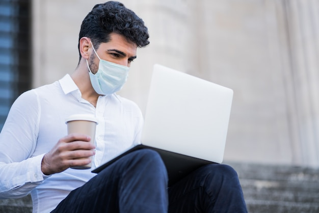 Retrato de homem de negócios usando máscara facial e usando seu laptop enquanto está sentado na escada ao ar livre. conceito de negócios