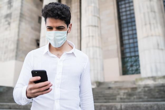 Retrato de homem de negócios, usando máscara facial e usando seu telefone celular em pé na escada ao ar livre. negócios e conceito urbano. novo conceito de estilo de vida normal.