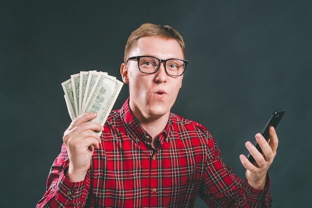 Retrato de homem de negócios vestido de maneira casual segurando a guarda do dinheiro, celebrando seu sucesso após fazer apostas online em um aplicativo de jogos de azar para celular