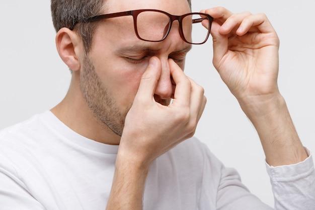 Retrato de homem de óculos, esfregando os olhos e a ponte do nariz, sente-se cansado depois de trabalhar no laptop, isolado