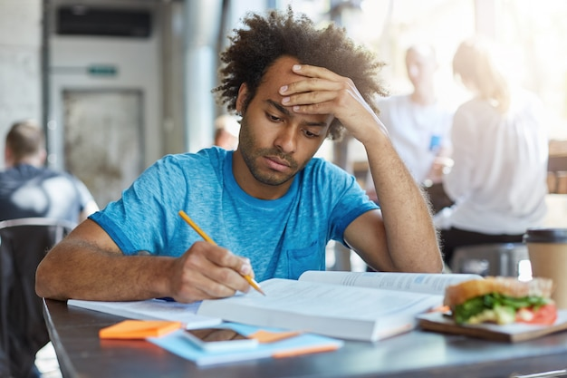 Retrato de homem de raça mista cansado e sério vestido casualmente sentado à mesa de madeira no café escrevendo notas e lendo livros almoçando, comendo hambúrguer, segurando a mão na cabeça tentando se concentrar