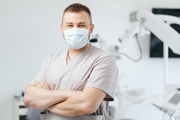 Retrato de homem dentista usando máscara médica com braços cruzados em clínica odontológica
