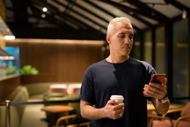 Retrato de homem dentro do café restaurante à noite, segurando a xícara de café e usando telefone celular, foto horizontal