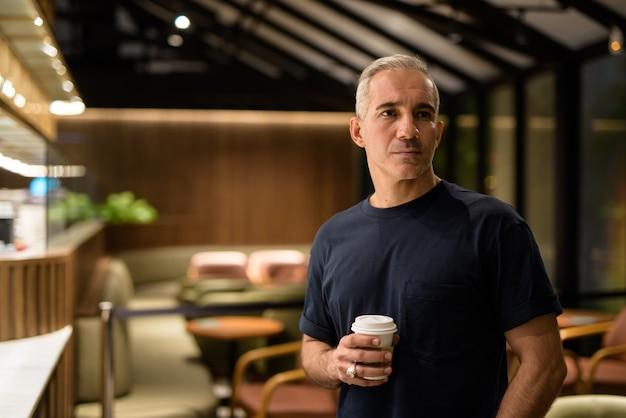 Retrato de homem dentro do café restaurante à noite, segurando a xícara de café, foto horizontal