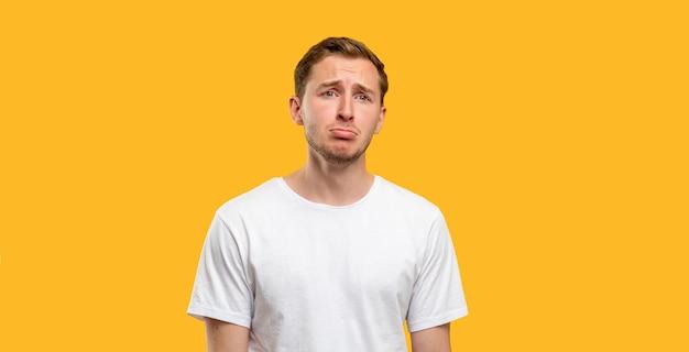 Retrato de homem deprimido. crise de solidão. cara infeliz em t-shirt branca isolada em fundo laranja.