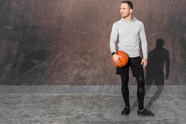 Retrato de homem desportivo com uma bola de basquete