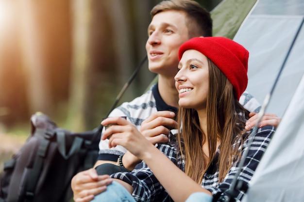 Retrato de homem e mulher aquecer, relaxar, beber chá quente na barraca ao ar livre em viagens de acampamento