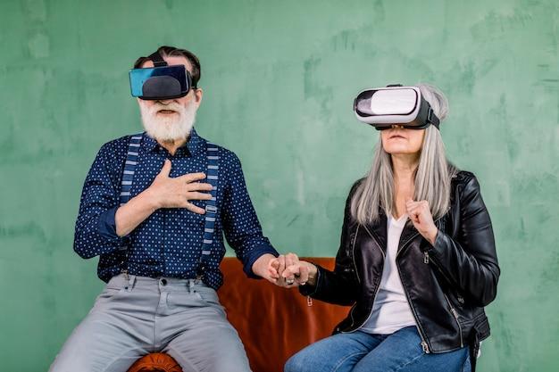 Retrato de homem e mulher idosos animados, sentados juntos na cadeira vermelha perto da parede verde, de mãos dadas e curtindo a realidade virtual usando óculos 3d especiais
