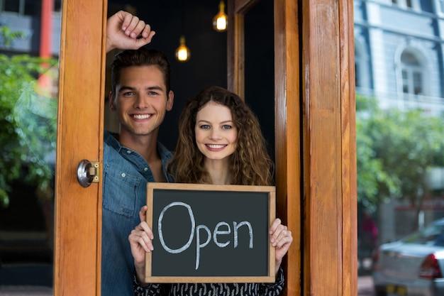 Retrato de homem e mulher mostrando lousa com sinal aberto