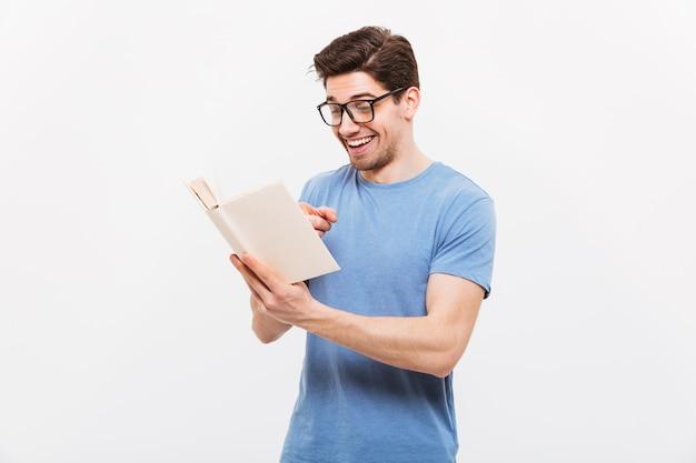 Retrato de homem educado na camisa azul, usando óculos, sorrindo enquanto lê um livro interessante, isolado sobre a parede branca