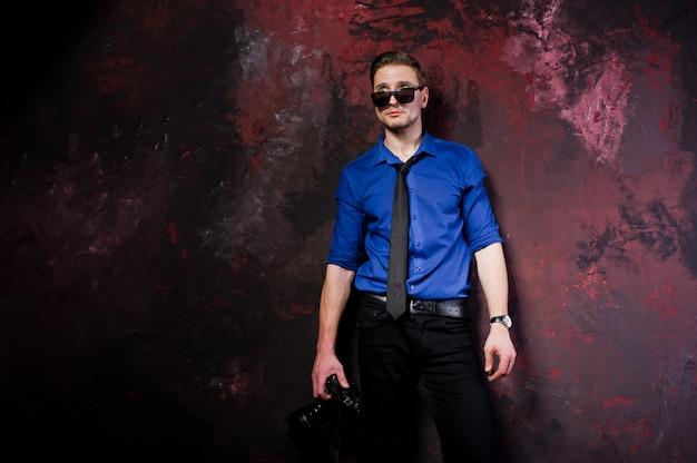 Retrato de homem elegante fotógrafo profissional com câmera, vestir camisa azul e gravata, óculos de sol.