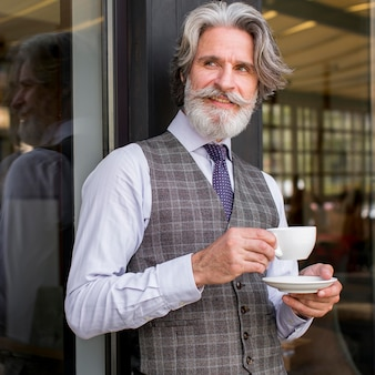 Retrato de homem elegante tomando café