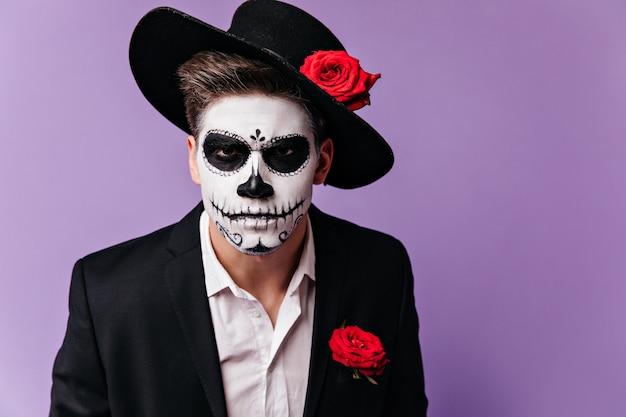 Retrato de homem em assustadora máscara de estilo mexicano, olhando severamente para a câmera.