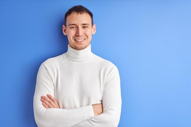 Retrato de homem em camisa branca casual, posando com os braços cruzados, sorrindo e olhando para a câmera isolada no fundo azul.