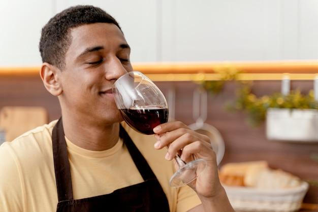 Retrato de homem em casa bebendo vinho