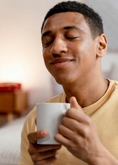 Retrato de homem em casa tomando café