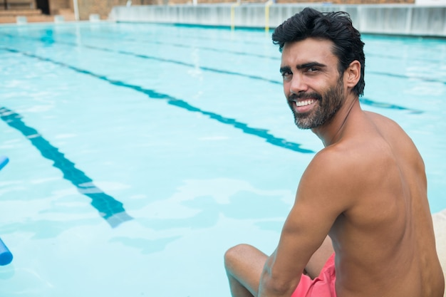 Retrato de homem em forma relaxando à beira da piscina