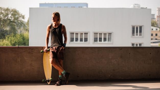 Retrato de homem em pé com um longboard e desviar o olhar