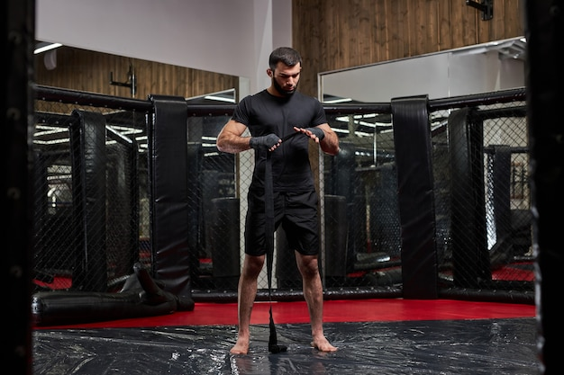 Retrato de homem em roupas esportivas pretas, preparando-se para uma luta difícil, envolvendo o punho em bandagens protetoras do esporte. de pé no ringue se preparando para a luta de mma
