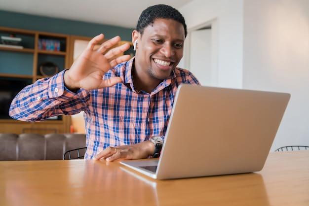 Retrato de homem em uma videochamada de trabalho com laptop de casa