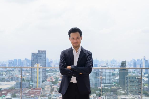 Retrato de homem empresário asiático vestindo terno ao ar livre em bangkok, tailândia