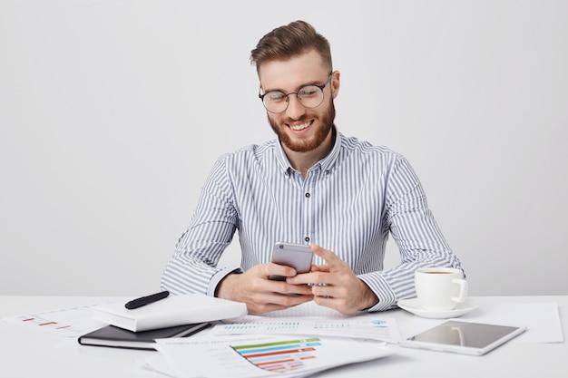 Retrato de homem encantador com a barba por fazer e penteado da moda, bate papo com a namorada nas redes sociais tem look alegre,