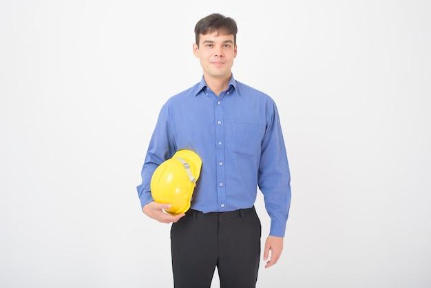Retrato de homem engenheiro com capacete de segurança amarelo está no branco