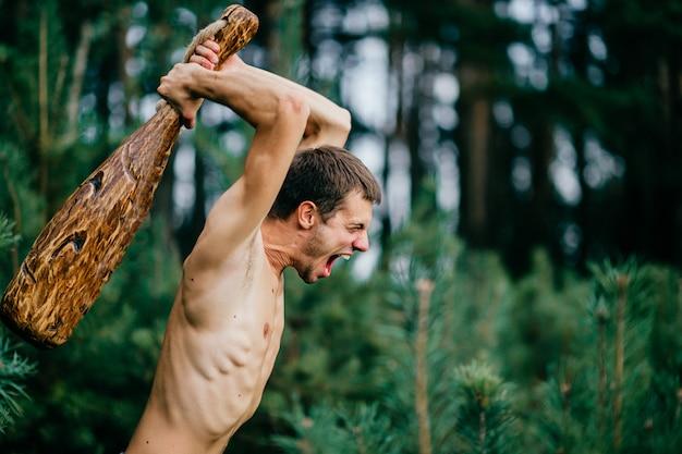 Retrato de homem engraçado com vara de madeira e selvagem expressão facial de caça na floresta
